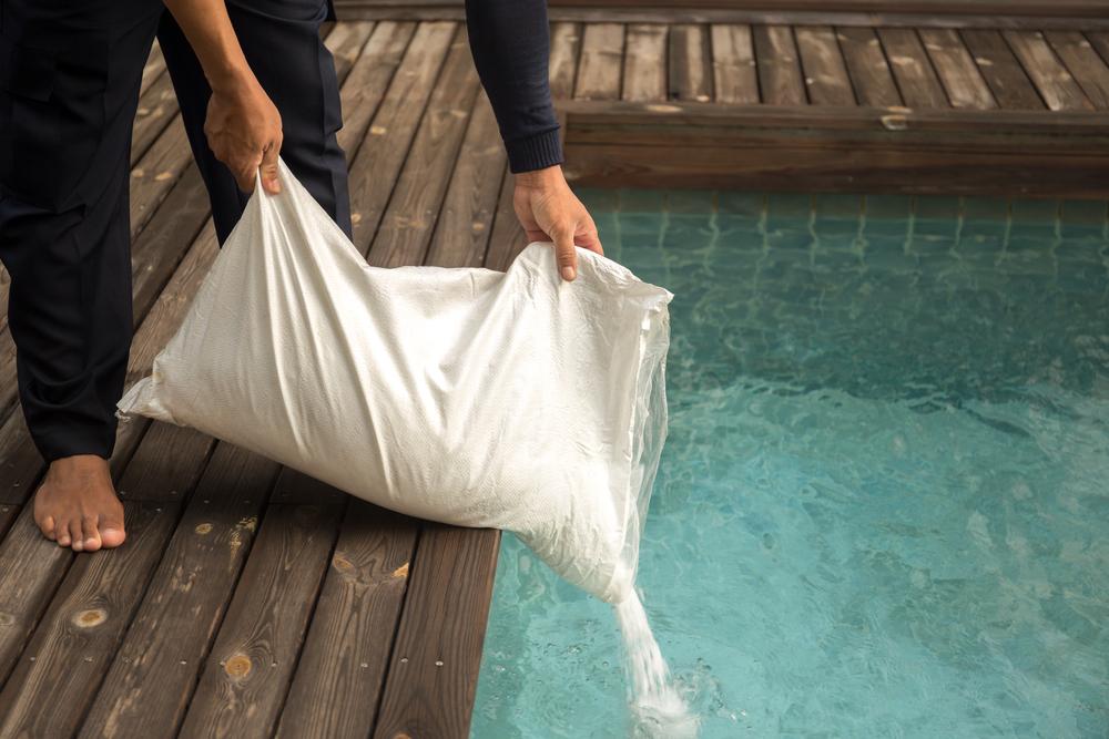 Ajout de chlore en poudre dans une piscine